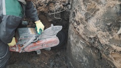 Worker with circular saw cutting concrete structure in ditch at building site Stock Footage