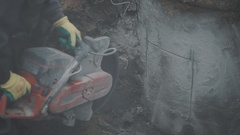 Lots of dust and fug producing by builder circular saw concrete in dirt ditch Stock Footage
