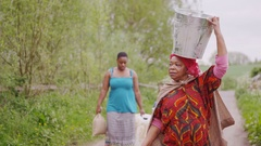 4K Family from African community carry containers to take water back to village Stock Footage