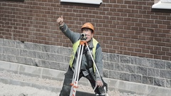 Builder in hard hat use theodolite and holds thumb up at building site Stock Footage