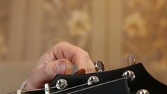 Musician tunes the guitar, hand closeup Stock Footage