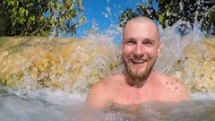 Young Bearded Man Smiling Under Waterfall at Emerald Pool Pond with Blue Water Stock Footage