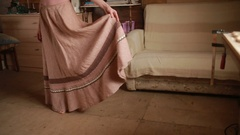 Girl measures the long skirt made of linen Stock Footage