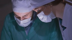 Doctors surgeons operate patient in operating theater, tilt down. Surgical team Stock Footage