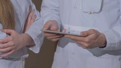 Doctor with colleagues examines the tablet cardiogram Stock Footage
