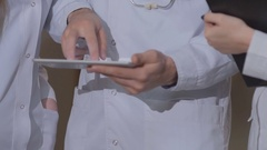 Close-up of doctor's hands, considering the patient's cardiogram on the tablet Stock Footage
