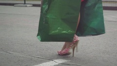 Shopaholic young woman in beautiful dress holding many shopping bags walking on Stock Footage