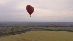 Hot air balloon in the sky over a wheat field.Aerial view Stock Footage
