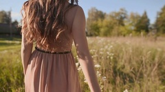Close-up beautiful girl with long hair goes in a green meadow, and touch the Stock Footage