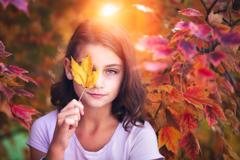 Portrait of young girl in rural setting, holding leaf in front of eye Stock Photos