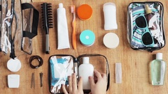 Hands packing cosmetic bag with stuff for travel Stock Footage