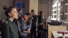 Model and make-up artist applying brush to model's face in makeup room Stock Footage
