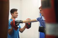 Male boxer training, punching teammate's punch mitt Stock Photos