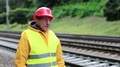 Railway man in red hard hat stands on railway track and smokes HD Footage
