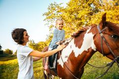 Little girl riding on a horseback with her mother walking nearby Stock Photos