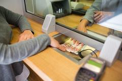 Clerk giving cash money to customer at bank office Stock Photos