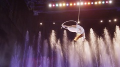 Aerial performer making acrobatic act against colorful fountains, acrobatics, Mo Stock Footage