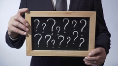 Question marks written on blackboard, male wearing classic suit holding a sign Stock Footage