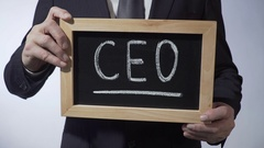 CEO written on blackboard, man in classic suit holding sign, business strategy Stock Footage