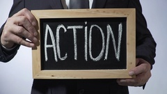 Action written on blackboard, man in black suit holding sign, business concept Stock Footage