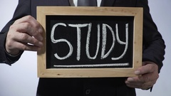 Study written on blackboard, businessman holding sign, career and future Stock Footage