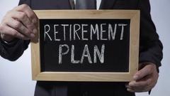Retirement plan written on blackboard, businessman holding sign, money savings Stock Footage