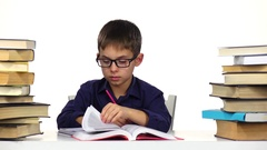 Boy sits at the table leafing through the book. White background Stock Footage