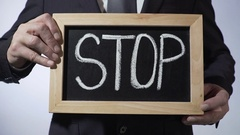 Stop written on blackboard, business person holding sign, motivation, honesty Stock Footage