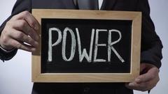 Power written on blackboard, businessman holding sign, business, politics Stock Footage