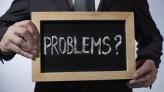 Problems with question mark written on blackboard, businessman holding sign Stock Footage
