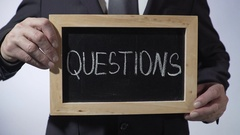Questions written on blackboard, business person holding sign, FAQ, advice Stock Footage