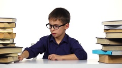 Boy sits at a table and reading a book. White background Stock Footage