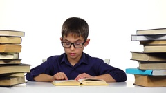 Little boy sits at a table and reads the book slowly. White background Stock Footage