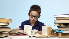 Boy with glasses sits at a table and excitedly that is looking for. Blue Stock Footage