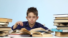 Leepy little boy sitting at a table and wearily leafing through a book. Blue Stock Footage