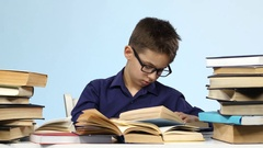 Boy sits at the table and wearily leafing through a book. Blue background Stock Footage