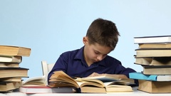 Boy sits at the table and falls asleep for a book. Blue background Stock Footage