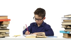 Boy sits at a table recording something into her notebook and flips through the Stock Footage