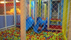 Child plays alone bored in ball pool play area Stock Footage