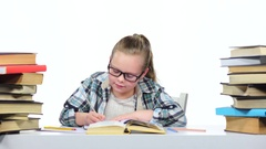 Girl sits at the table leafing through the book. White background Stock Footage