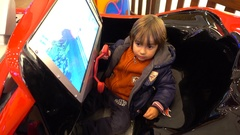 Kid bored driving an amusement machine Stock Footage