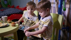 Little twin kids brothers at home watch tablet cartoons sit at table with sweets Stock Footage