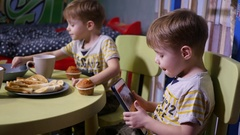 Little twin kids brothers at home watch tablet cartoons eating sweets candies Stock Footage