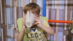 Little twin kid brother at home watch tablet cartoons drinking tea from cup Stock Footage
