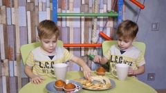 Funny kids little twins brothers at home eating sweets bananas sit at table Stock Footage