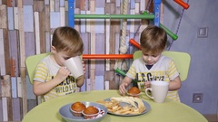Funny kids little twins brothers at home eating sweets bananas and cake Stock Footage