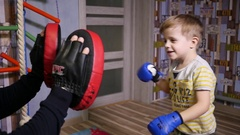 Father teach little twin kid boy fighting with boxing gloves at home slow motion Stock Footage
