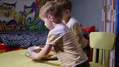 Little twin kids brothers at home watch tablet cartoons eating sweets drinkin Stock Footage