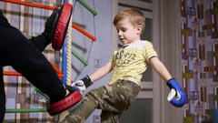 Father teach little twin kid boy fighting with boxing gloves at home Stock Footage