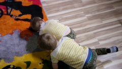 Twin kids boys enjoy playing fighting with boxing gloves at home roll on floor Stock Footage